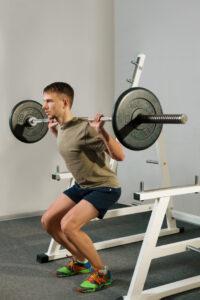Atleta che fa gli squat con pesi